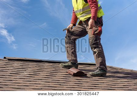 Unrecognizable Workman Standing On Tile Roof Of New Home Under Construction Against Blue Sky With He