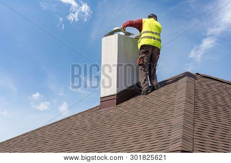 Skilled Workman In Protective Work Wear And Special Uniform Install Chimney On Roof Top Of New House
