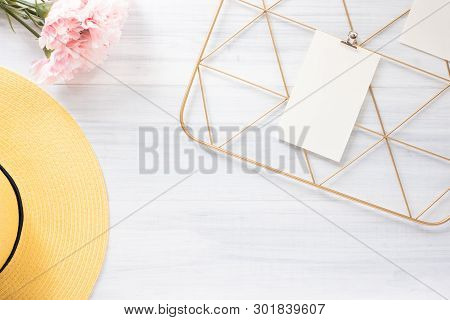 Top View Note Pad Clip Frame And Summer Yellow Hat With Pink Flower On White Wood Table.summer Vacat