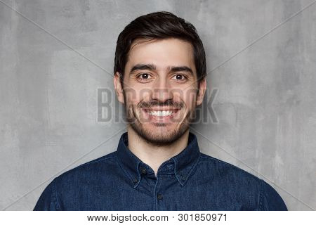 Headshot Portrait Of Smiling Young Man Isolated On Gray Wall Background