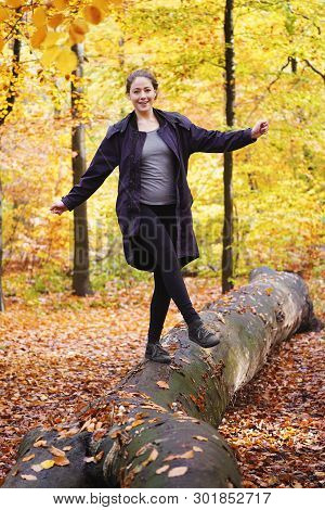 Happy Carefree Young Woman Balancing On Tree Trunk In Forest - Enjoying Active Lifestyle In Fall Sea