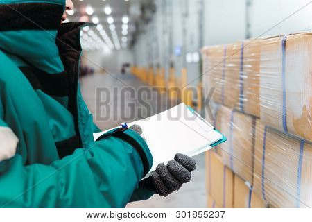 Hand Of Worker With Clipboard Checking Goods In Freezing Room Or Warehouse. Export-import Logistics