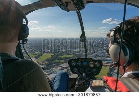 View From Flying Helicopter On Over City. Pilot And Man In The Helicopter Flying Over Urban Areas. S