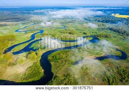 Aerial View On Curved River Through White Clouds. River On Green Meadow From Above. Mist River. Fogg