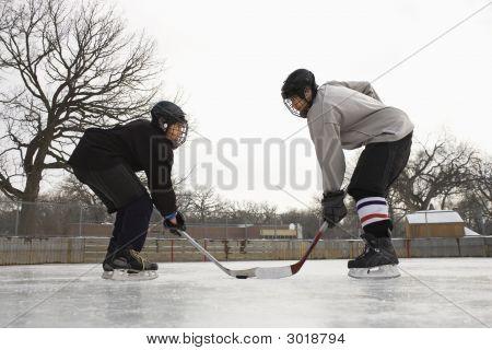 Eishockeyspieler stehen sich gegenüber.