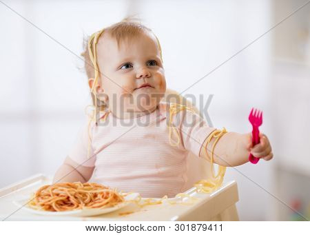 Funny Baby Eating Noodle. Grimy Kid Eats Spaghetti With Fork Sitting On Table At Home