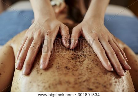 Beauticican applying fine coffee scrub on back of female client in spa salon poster