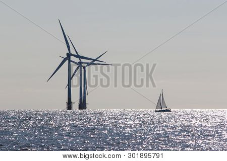 Wind Power. Environmentally Friendly Sailing Yacht. Offshore Windfarm Turbines. Tranquil Scene Of Re