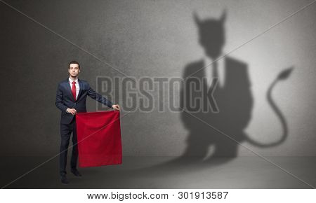 Businessman standing with red cloth in his hand and devil shadow on the background