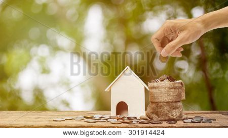 Saving Money, Home Loan, Mortgage, A Property Investment For Future Concept. A Man Hand Putting Mone