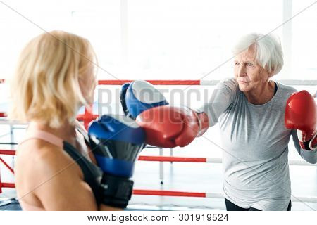 Senior female in activewear and boxing gloves kicking her young rival while both preparing for sports competition
