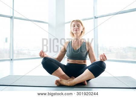 Mature blonde active woman in tracksuit crossing her legs while sitting in pose of lotus and meditating in gym