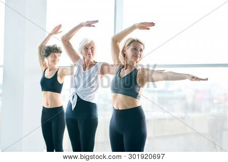 Young, middle aged and senior females in activewear standing in row while practicing exercise for stretching