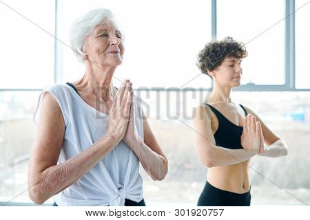 Active senior female in sportswear keeping her hands put together by chest while practicing relaxing yoga exercise in gym