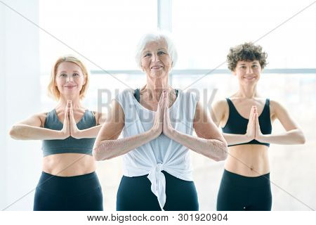 Senior white-haired active woman and her yoga groupmates putting their hands together by chest while keeping balance