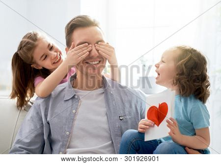 Happy father's day! Children daughters congratulating dad and giving him postcard. Daddy and girls smiling and hugging. Family holiday and togetherness.