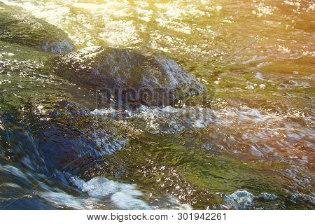 Picturesque stones in the turbulent flow of the river under the sun. poster