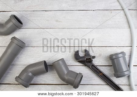 Fittings, Pipe, Valves, Plastic Pipe For Water, Water Hose, Adjustable Wrench On The Wooden Backgrou