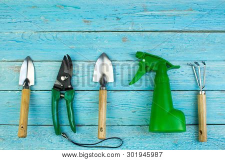 Composition With Flowers And Gardening Tools On The Wooden Background With Space For Text