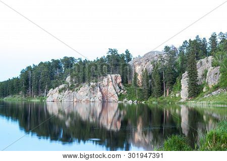 Calm Waters Of Stockade Lake Reflecting The Rocks And Trees Of A Dynamic Shoreline With An Isolated