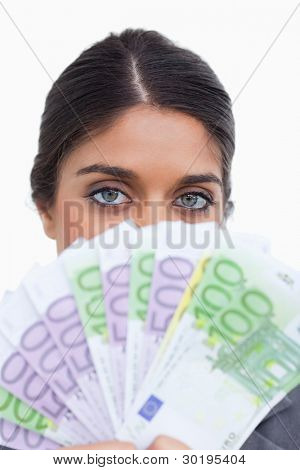 Close up of female entrepreneur hiding her face behind money against a white background
