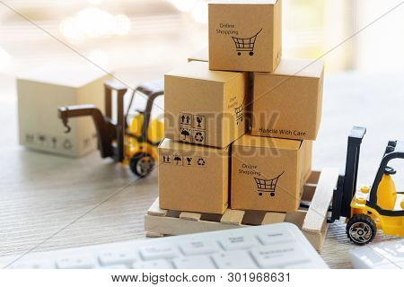 Mini Forklift Truck Load Stack Of Cardboard Boxes With Text Online Shopping And Symbols On Wooden Pa