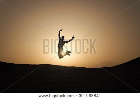 Achieve Main Goal. Silhouette Man Motion Jump In Front Of Sunset Sky Background. Future Success Depe