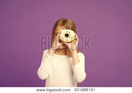 Sweet mood. Child look in donut on violet background. Little girl with glazed ring doughnut on purple background. Kid with junk food. Food and dessert. Childhood and childcare, copy space. poster