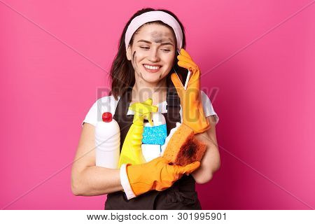 Positive Caucasian Woman Speaking On Mobile Phone While Clening Her House, Holding Sponge And Deterg