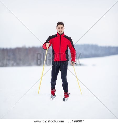 Cross-country skiing: young man cross-country skiing on a lovely snowy winter day