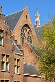 The external facade of Grote of Sint Jacobskerk with the turret of Oude Stadhuis (Old Town Hall, 16 century) in the background, The Hague, Netherlands poster