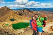 New Zealand Tongariro Alpine Crossing Hiking tourists couple selfie at Emerald Lakes. Happy backpackers tramping taking phone photo of themselves at volcanic mountains. Tramping track of New Zealand. poster