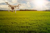 UAV drone multicopter flying with high resolution digital camera over a crops field, agriculture concept poster