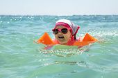 Laughing Girl Toddler Wearing Sunglasses And Inflatable Armbands Swimming In The Sea poster