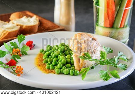 White Dish With Fried Chicken Breast And Broiled Green Peas  On The Dark Background.white Bread And