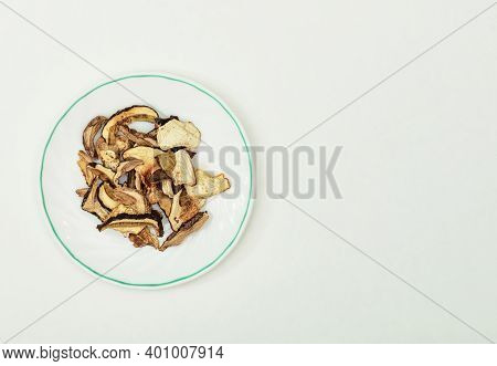 Dried Autumn Boletus, Porcini Mushrooms In A Saucer On A Sheet Of Paper, White Background, Free Spac