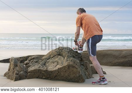 Mature Runner Tying Shoelace On A Rock At A Beach