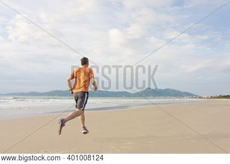 Mature Man Running On A Long Beach Early In The Morning