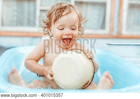 A Little Boy Is Bathing In A Bath On The Street Near A Country House