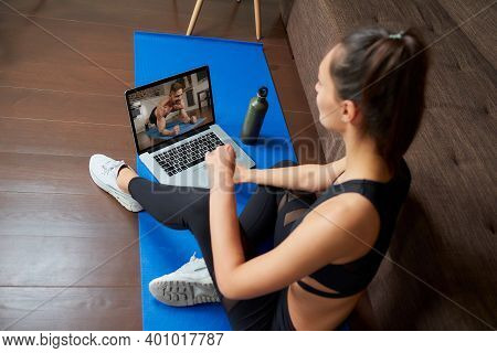 A Laptop Screen View Over A Woman's Shoulder. A Sporty Girl In A Tight Suit Is Watching A Workout Vi