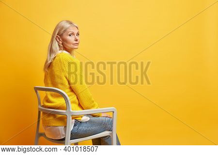 Sideways Shot Of Calm Beautiful Fifty Years Old Woman Sits On Chair Being Alone Thinks About Life We