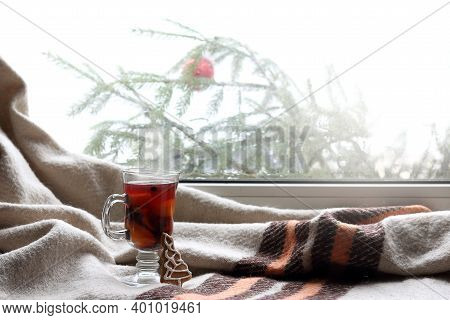 Mulled Wine In A Glass And A Ginger Tree On The Background Of A Plaid By The Window In Winter. Warmi