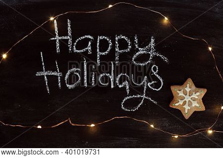 Gingerbread Cookie And Chalk Inscription Of Happy Holidays On A Dark Surface With Garland Lights. Co