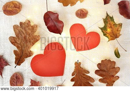 Two Red Hearts Surrounded By Autumn Leaves With Backlit Garlands. Favorite Time Of The Year For Dati