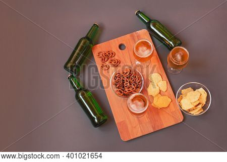 Glasses Of Beer, Bottles Of Beer And Beer Snacks On Cutting Board On Gray Background. Top View, Copy