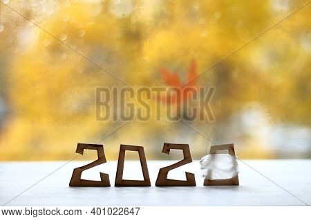 Number 2020 With The Last Digit Wearing A Medical Mask Against A Blurred Autumn Landscape. Time For