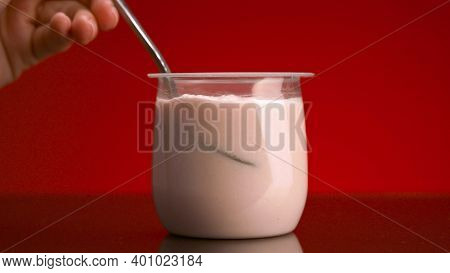 Close-up Of Yogurt In Glass Cup On Red Background. Stock Footage. Hand With Spoon Takes Yogurt From