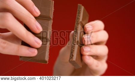 Man Breaking Chocolate. Stock Footage. Close-up Of Hands Breaking Chocolate Bar Into Two Parts. Deli