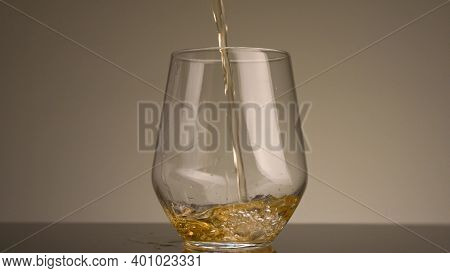 Close-up Of Yellow Liquid Being Poured Into Transparent Glass. Stock Footage. Yellow Drink Is Poured