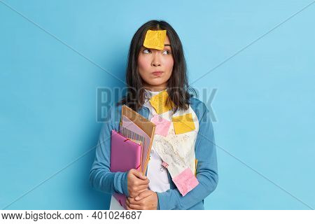 Thoughtful Asain Woman Has Sticky Notes On Clothes And Forehead Stads Pensive Works Hard During Dead